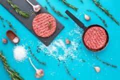 新鲜的未加工的牛肉肉用草本和盐在绿松石背景 免版税图库摄影