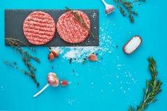 新鲜的未加工的牛肉肉用草本和盐在绿松石背景 免版税库存照片