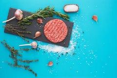 新鲜的未加工的牛肉肉用草本和盐在绿松石背景 库存照片