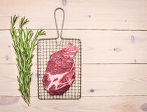 新鲜的未加工的猪肉牛排用在格栅的迷迭香烤的在一个白色土气木桌边界,地方文本顶视图 库存照片