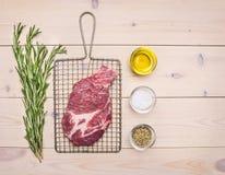 新鲜的未加工的猪肉牛排用在格栅的迷迭香烤的用香料、黄油和草本在白色土气木桌边界, 库存照片