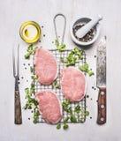 新鲜的未加工的猪肉牛排用草本、一把刀子和叉子肉的在格栅烤的木土气背景顶视图 免版税库存图片