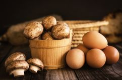 新鲜的未加工的皇家蘑菇和鸡蛋在黑暗的木土气桌上 免版税图库摄影