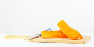 新鲜的未加工的红萝卜Halfs与一把刀子的在切板 库存图片