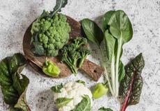 新鲜的未加工的蔬菜-硬花甘蓝,花椰菜,唐莴苣,在轻的背景的胡椒 图库摄影