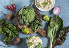 新鲜的未加工的蔬菜-硬花甘蓝,花椰菜,唐莴苣,胡椒,甜菜,在蓝色背景的葱 库存图片