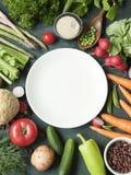新鲜的未加工的蔬菜vareity围拢的一块白色板材在r的 免版税库存图片