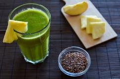 新鲜的未加工的绿色菠菜圆滑的人用菠萝、苹果和种子 库存图片