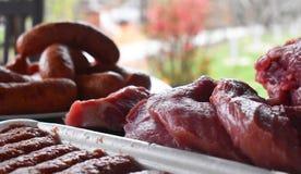 新鲜的未煮过的红肉、香肠和丸子在准备好木的桌上被烹调在室外火格栅 在的烤肉 免版税库存照片