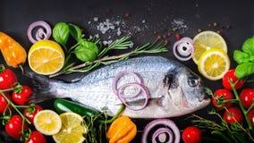 新鲜的未煮过的鱼、dorado、海鲷用柠檬,草本、菜和香料在石背景 顶视图 钞票 免版税库存图片