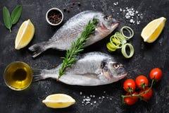 新鲜的未煮过的dorado或海鲷鱼与柠檬切片、香料、草本和菜 bufala食物意大利地中海无盐干酪 顶视图 库存图片