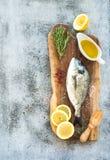新鲜的未煮过的dorado或海鲷鱼用柠檬、草本、油和香料在土气木板在难看的东西背景 库存照片