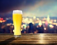 新鲜的未过滤的啤酒和香港blured lighhts  库存图片