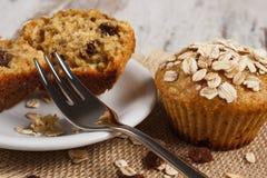 新鲜的松饼用燕麦粥烘烤了用在白色板材,可口健康点心的全麦的面粉 库存图片