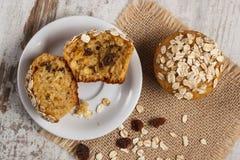 新鲜的松饼用燕麦粥烘烤了用在白色板材,可口健康点心的全麦的面粉 免版税库存图片