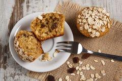 新鲜的松饼用燕麦粥烘烤了用在白色板材,可口健康点心的全麦的面粉 免版税库存照片