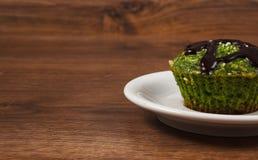 新鲜的松饼用菠菜、被脱水的椰子和巧克力釉,可口健康点心,文本的拷贝空间 库存图片