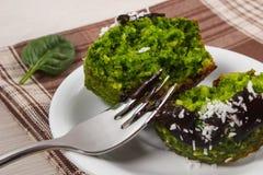 新鲜的松饼用菠菜、被脱水的椰子和巧克力釉,可口健康点心 图库摄影