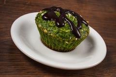 新鲜的松饼用菠菜、被脱水的椰子和巧克力釉,可口健康点心 免版税库存图片
