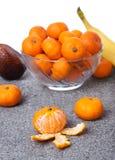 新鲜的柑桔结果实剥皮与在垂直的玻璃碗 免版税库存图片