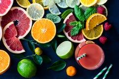 新鲜的柑橘切片和汁在黑背景顶视图 免版税库存照片