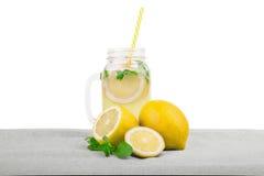 新鲜的柑橘柠檬水用明亮的黄色柠檬,薄菏绿色叶子在玻璃的在一张灰色桌上,隔绝在白色背景 免版税图库摄影