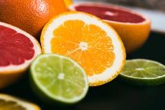 新鲜的柑橘stihli 柠檬、石灰、葡萄柚和桔子在黑背景 免版税库存照片
