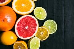 新鲜的柑橘stihli 柠檬、石灰、葡萄柚和桔子在黑背景 库存照片