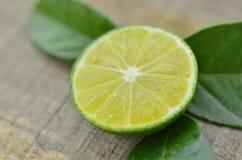 新鲜的柠檬削减了与叶子的切片在木背景 库存图片