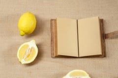 新鲜的柠檬和被打开的笔记本 库存图片
