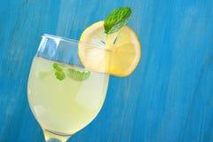 新鲜的柠檬汁在玻璃和蓝色木背景中 库存图片