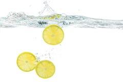 新鲜的柠檬滴下了入与在白色隔绝的飞溅的水 库存照片