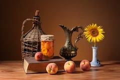 新鲜的桃子、书、瓶子和花向日葵 库存照片