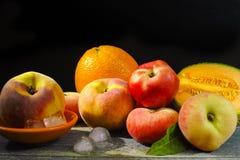 新鲜的桃子、瓜和桔子在冰,热的夏天概念 库存图片