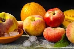 新鲜的桃子、瓜和桔子在冰,热的夏天概念 免版税库存图片