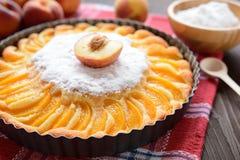 新鲜的桃子饼洒与在木背景的糖 免版税库存图片