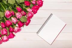 新鲜的桃红色玫瑰花和倒空在木甲板的白色笔记本 图库摄影