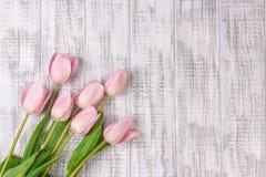 新鲜的桃红色郁金香开花在白色木土气桌上的花束 库存照片
