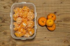 新鲜的桔子保留在木背景的塑料盒 免版税库存照片