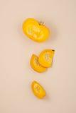 新鲜的桔子切了在轻的米黄淡色背景的南瓜 免版税库存图片