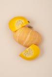 新鲜的桔子切了在轻的米黄淡色背景clos的南瓜 免版税库存照片