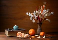 新鲜的桔子和干花在花瓶 免版税库存照片