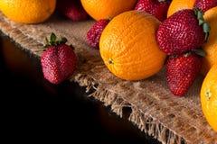 新鲜的桔子和成熟草莓在黄麻布料右边高c 免版税库存照片
