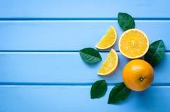 新鲜的桔子和汁液在蓝色木头 免版税库存照片