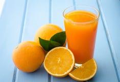 新鲜的桔子和汁液在蓝色木头 免版税图库摄影
