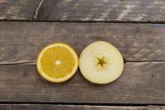 新鲜的桔子和苹果在一张木书桌上 免版税库存照片