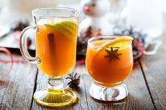 新鲜的桔子和苹果汁与橙色切片、茴香和cinna 免版税库存图片