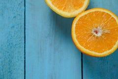 新鲜的桔子对分在蓝色木背景的果子与拷贝空间 免版税库存图片