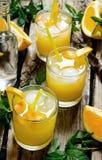 从新鲜的桔子的三个鸡尾酒与冰和在木背景的薄荷叶 库存照片