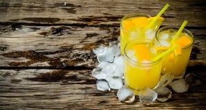从新鲜的桔子的三个鸡尾酒与冰和秸杆在木背景 文本的空位 免版税图库摄影